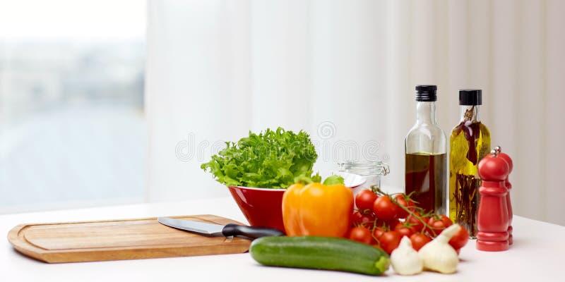 Grönsaker, kryddor och kitchenware på tabellen royaltyfri bild