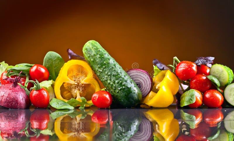 Grönsaker med arugula och spenat på den svarta tabellen arkivfoton