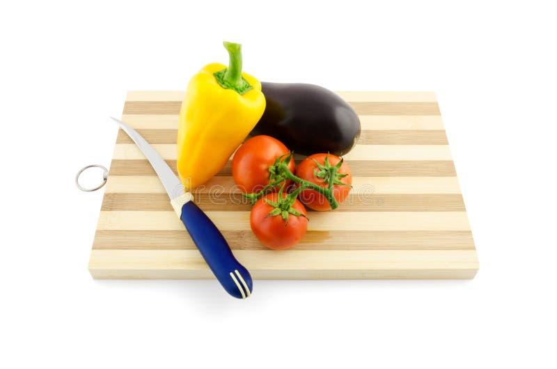 Grönsaker med kniven på skrivbordet som isoleras på vit royaltyfri bild