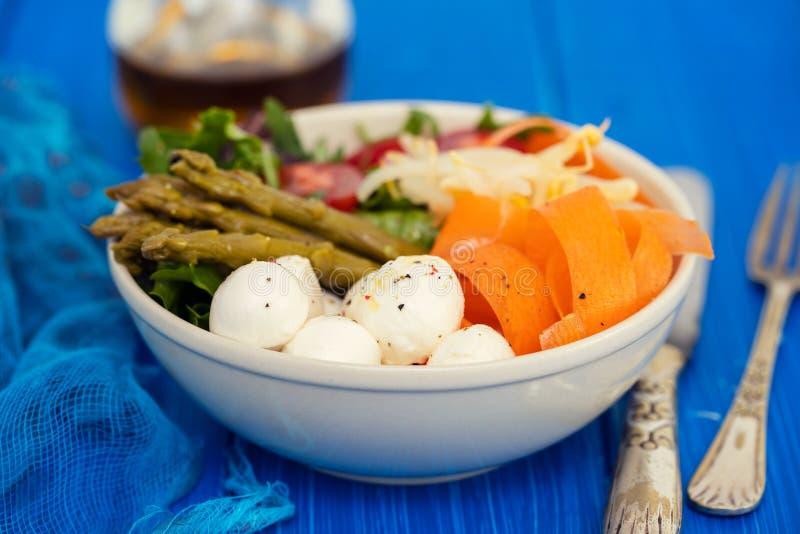 Grönsaker med ost i liten bunke på blå bakgrund royaltyfri fotografi