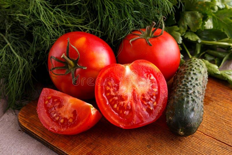 Grönsaker, mogna röda tomater och gröna gurkor arkivbilder
