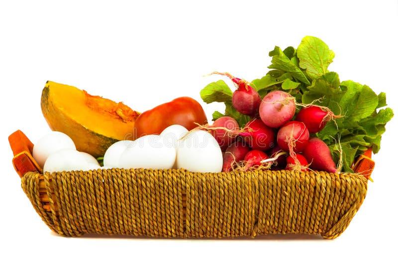 Grönsaker och ägg på en korg som isoleras på vit royaltyfria foton