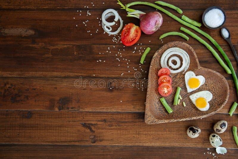 Grönsaker och en platta med stekte ägg på övre fors för träslut för bakgrund över huvudet royaltyfri bild