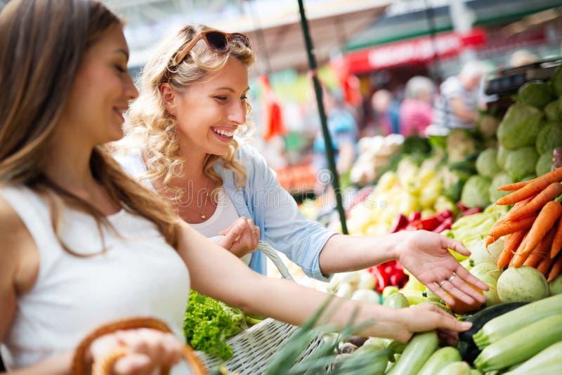 Grönsaker och frukter för vänner för unga kvinnor skälla på marknaden arkivbilder