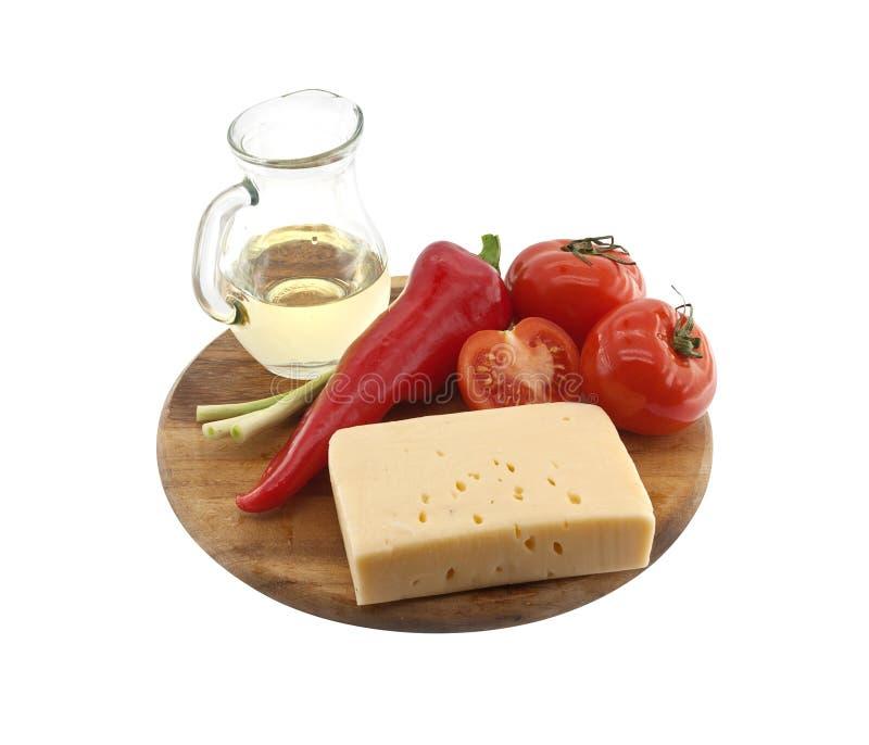 Grönsaker, olja och ost på skärbrädan som isoleras på vit royaltyfri bild
