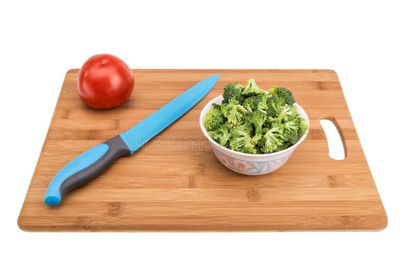 Grönsaker på en skärbräda och en kniv arkivfoton