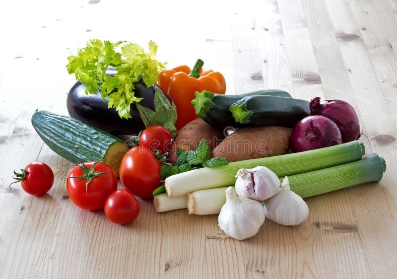 Grönsaker på ett sunlit köksbord arkivbild