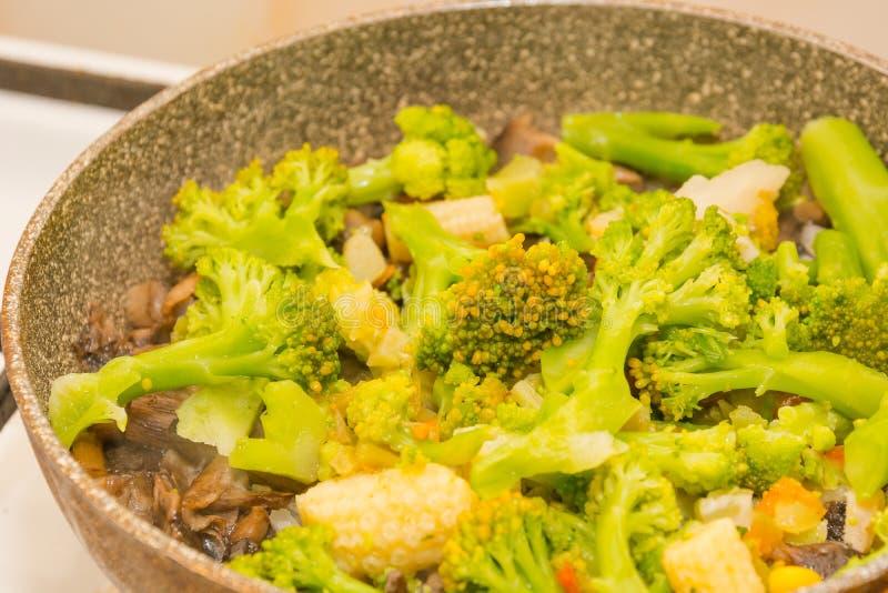 Grönsaker stekas i en panna Förberedelse av grönsaker Grönsakragu arkivfoto