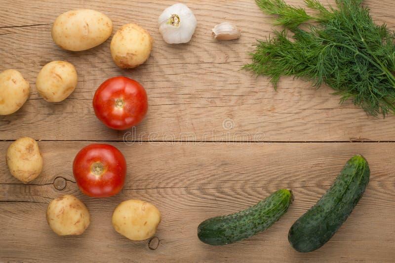 Grönsaker tomater, gurkor, potatisar, dill, vitlök på en träbakgrund med tomt utrymme för att skriva arkivfoton