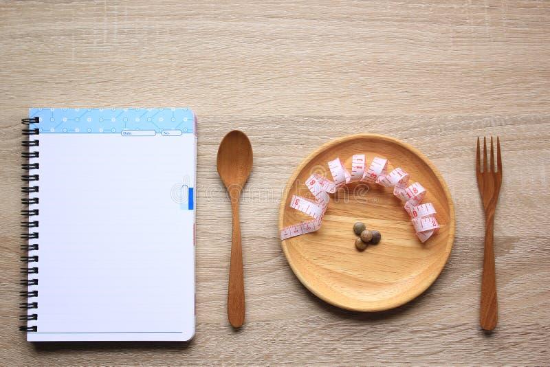 Grönsakkulor och måttbandet i träbunken med sked- och gaffelträ och den tomma anteckningsboksidan, sunt äta och bantar fotografering för bildbyråer