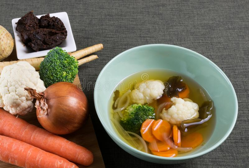 Grönsakmisosoppa med löken, moroten, blomkålen, broccoli och havsväxt i grön maträtt på brun bordduk och nya grönsaker arkivbild