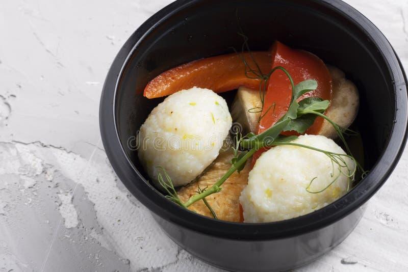 Grönsakrullar, linser och ångad fisk med persilja i svart plast- matbehållare arkivbild