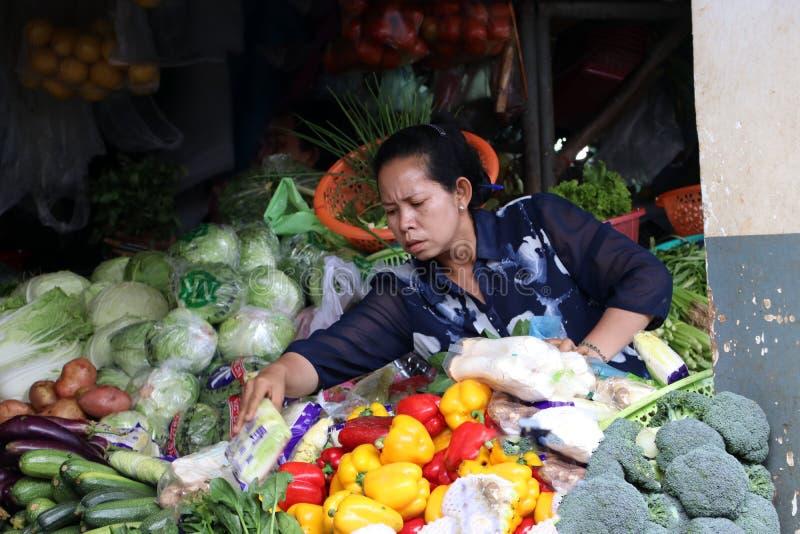 Grönsaksäljaren på den centrala marknaden, en stor marknad med otaligt stannar av gods royaltyfri bild