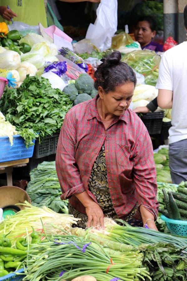 Grönsaksäljaren på den centrala marknaden, en stor marknad med otaligt stannar av gods royaltyfria bilder