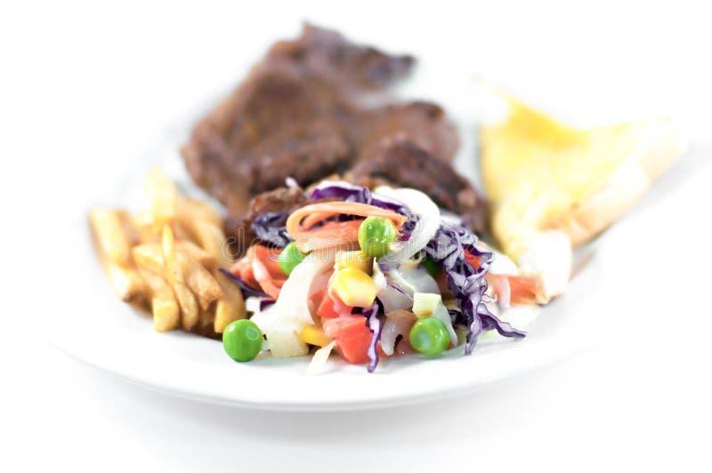 Grönsaksallad i nötköttbiff och pommes frites med ostbröd arkivfoto