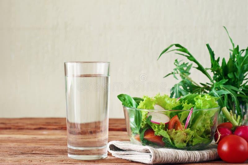 Grönsaksallad med ett exponeringsglas av rent vatten arkivbild