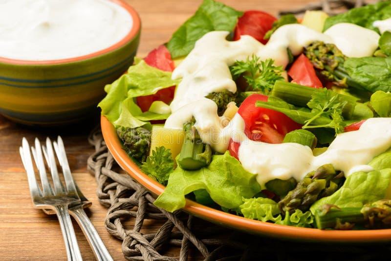 Grönsaksallad med sparris, unga potatisar, grönsallat, tomater och spenat, tjänade som med vitlöksås royaltyfri fotografi