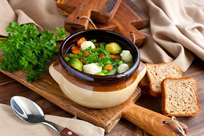 Grönsaksoppa med moroten, blomkålen, persilja, Bryssel groddar och bönor över lantlig träbakgrund royaltyfri fotografi