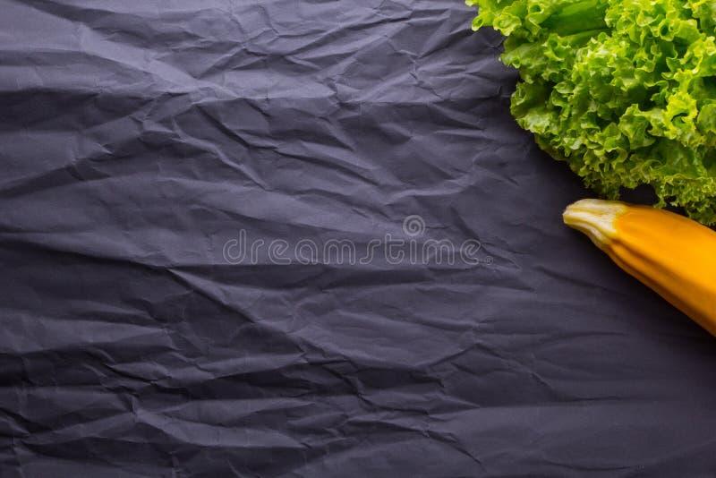 Grönsallat och zucchini på svart pappers- bakgrund Med avstånd för text royaltyfri foto