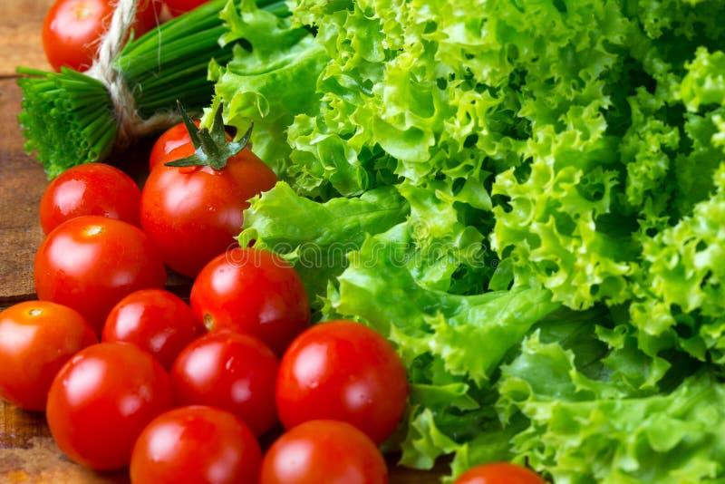 Grönsallatsallad, tomater och gräslökar på träbakgrund fotografering för bildbyråer