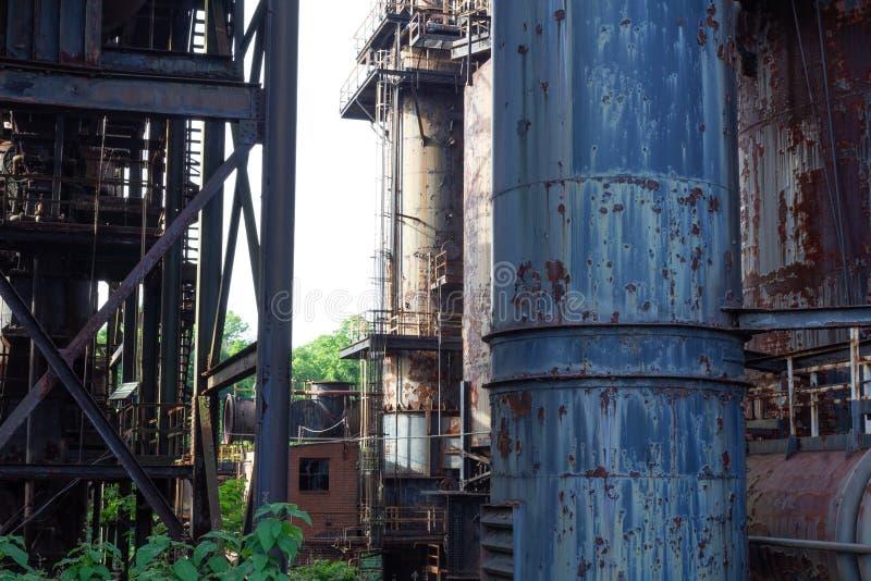 Grönska som växer upp till och med ett övergett industriellt komplex och att skala målarfärg och rostade rör arkivbilder