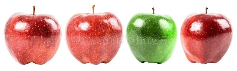 Grönt äpple bland röda äpplen arkivbilder