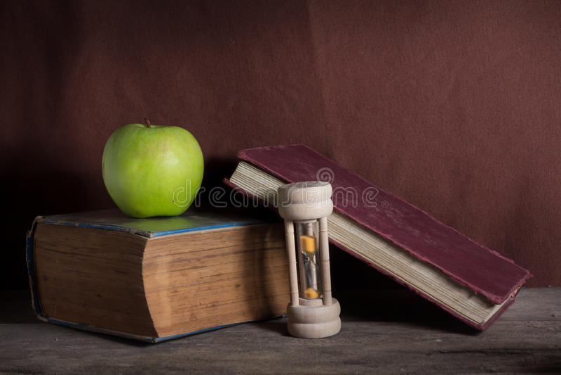 Grönt äpple för stilleben med böcker och timglas royaltyfria bilder