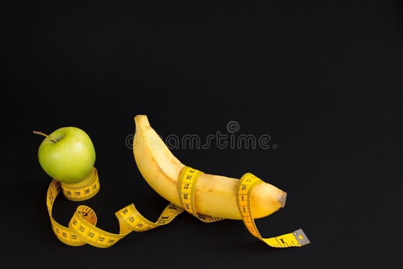 Grönt äpple, gul banan och mätaband med cm och tum som isoleras på svart bakgrund arkivbild