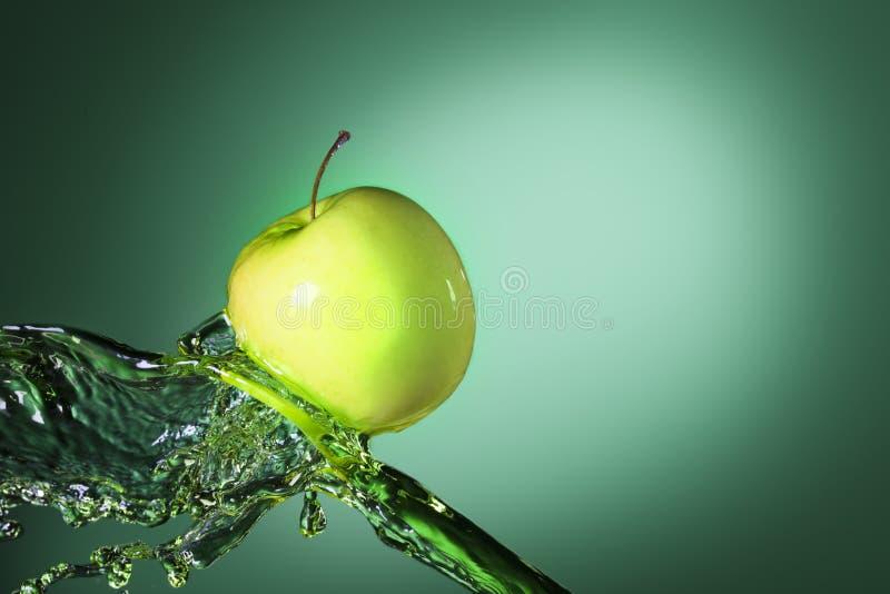 Grönt äpple i fruktsaftström royaltyfri foto