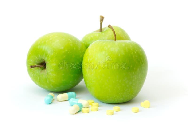 Grönt äpple med bantningpills royaltyfri bild