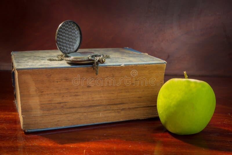 Grönt äpple med den antika boken och klockan fotografering för bildbyråer