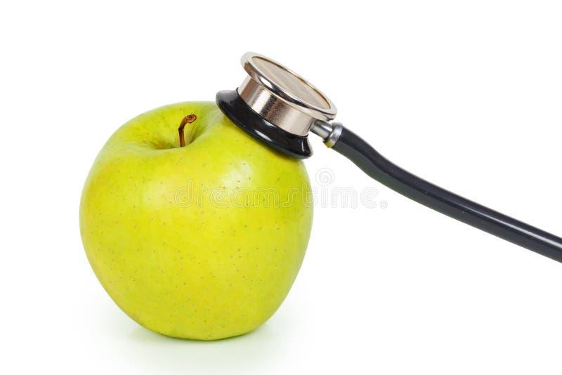 Grönt äpple och blodtryckmeter fotografering för bildbyråer