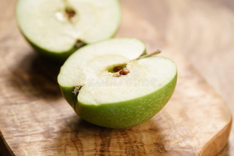 Grönt äpple på den wood brädecloseupen royaltyfri foto