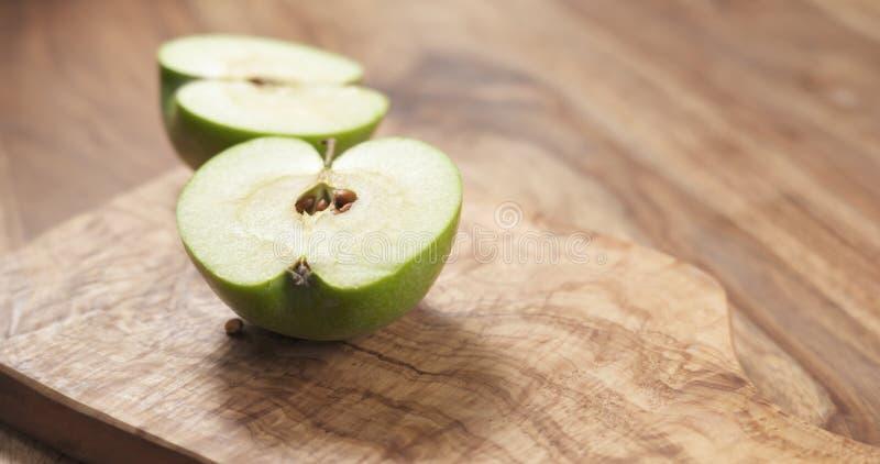 Grönt äpple på det wood brädet fotografering för bildbyråer