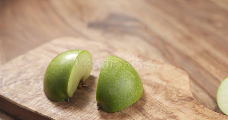 Grönt äpple på det wood brädet arkivfoton