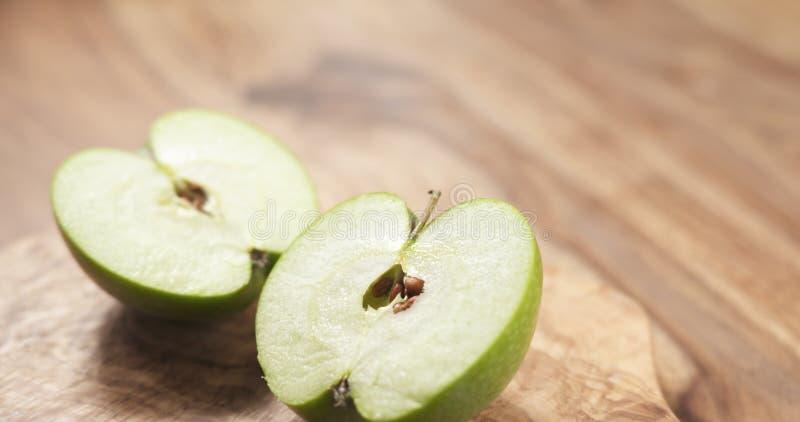 Grönt äpple på det wood brädet arkivfoto