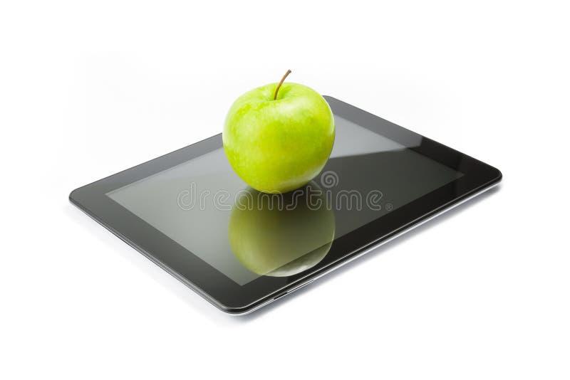 Grönt äpple på digital minnestavlaPC på vit bakgrund royaltyfri fotografi