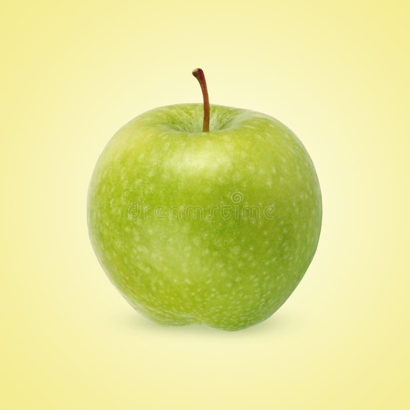 Grönt äpple på en gul bakgrund royaltyfria foton