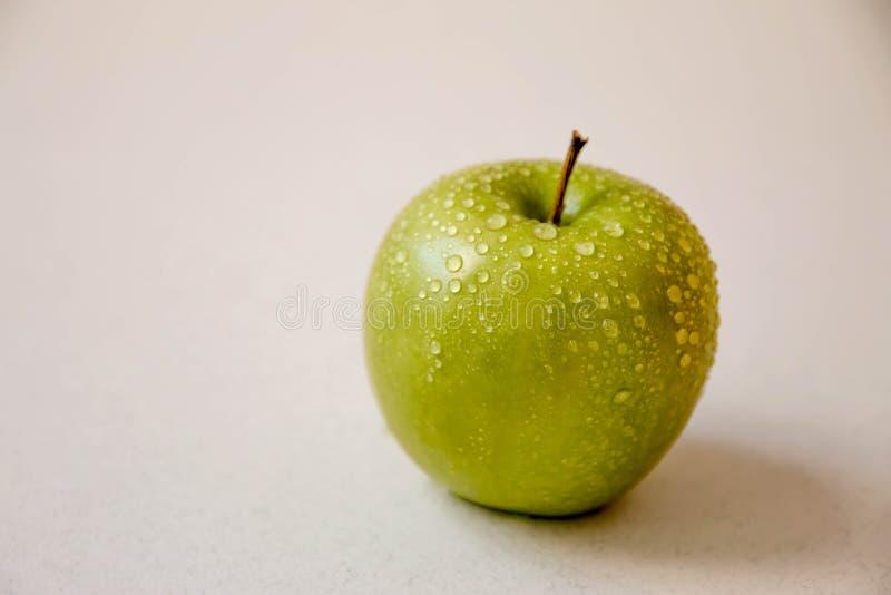 Grönt äpple på en vit bakgrund, med vattensmå droppar arkivfoto