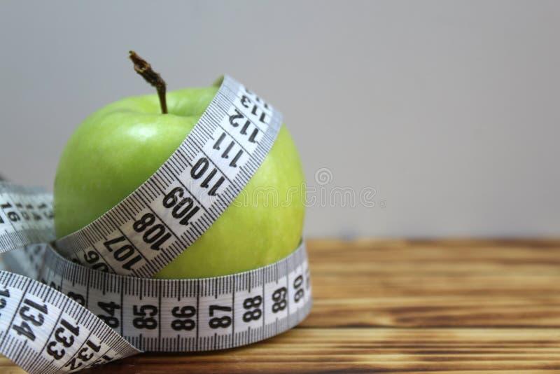 Grönt äpple som vrids, genom att mäta bandet arkivbilder