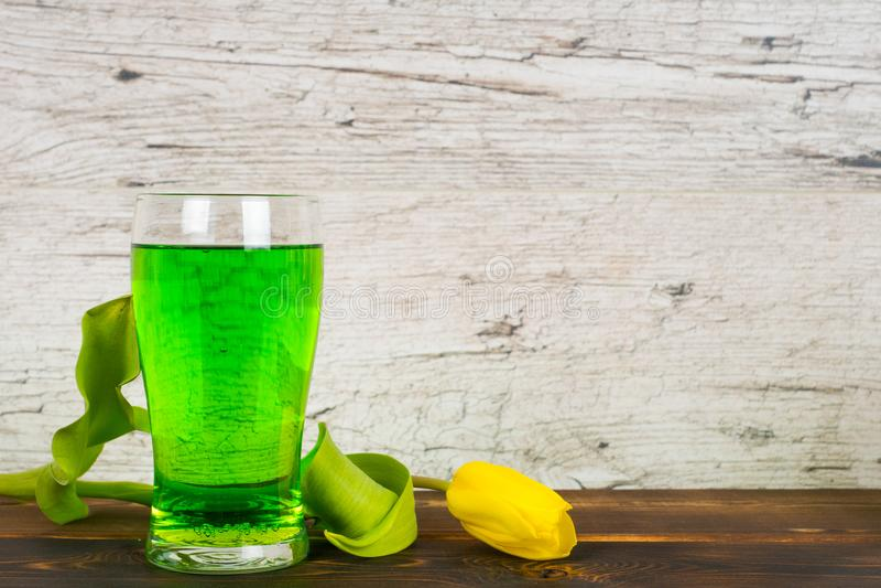 Grönt öl i exponeringsglas med tulpan arkivfoto