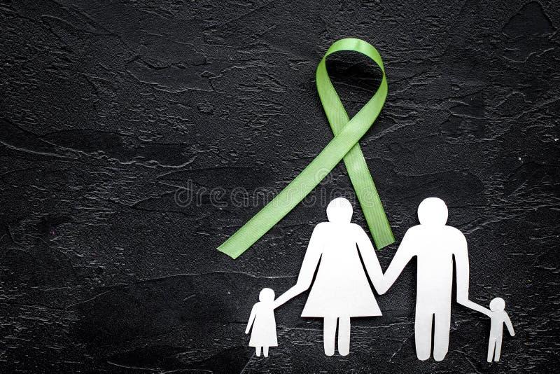 Grönt band för den Lyme sjukdomen, njurecancer, kontur för medvetenhet för organdonation near pappers- av familjen på svart fotografering för bildbyråer