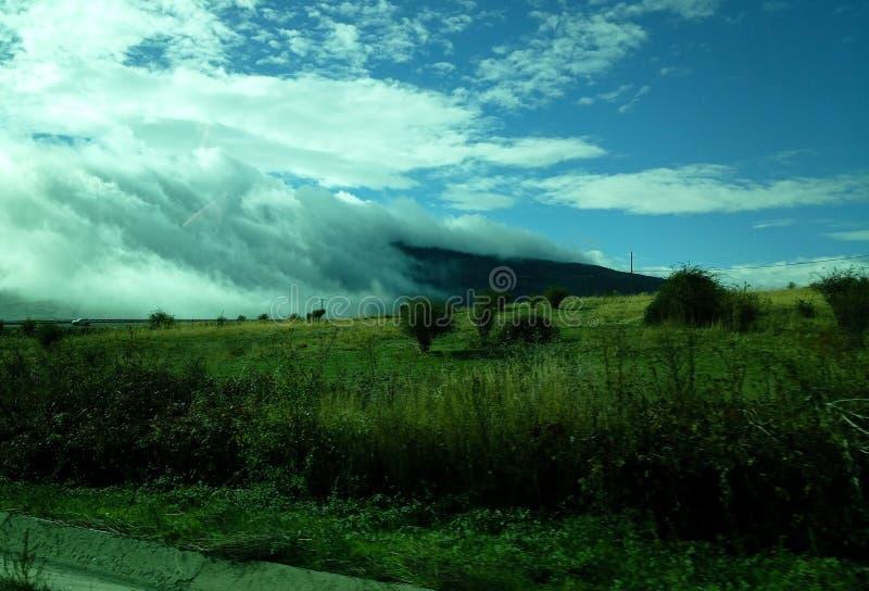 Gr?nt berg som sl?s in av moln arkivfoto