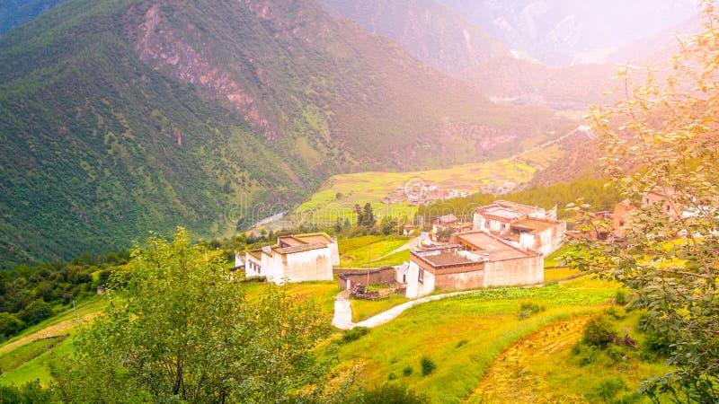 Grönt bergigt landskap av Tibet med den lilla traditionella tibetana byn royaltyfria foton