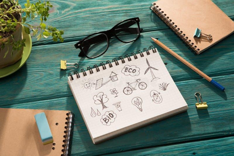 Grönt energibegrepp - notepaden med skissar på skrivbordet arkivbild
