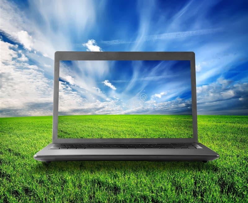 Grönt fält och bärbar dator royaltyfria foton
