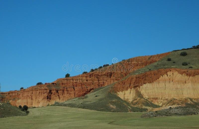 Grönt fält och berg av saragosaen arkivfoto