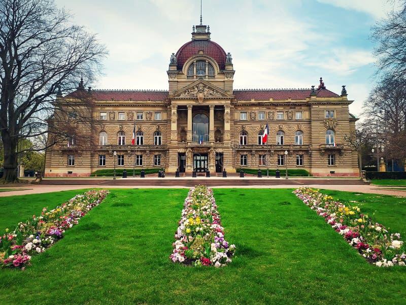 Grönt gräs och blommor framme av Palais du Rhin Strasbourg republikfyrkant arkivfoto