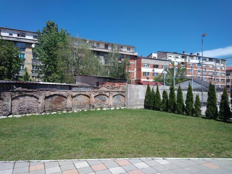 Grönt gräs, tegelstenvägg och byggande bakom i Pirot, Serbien royaltyfri fotografi