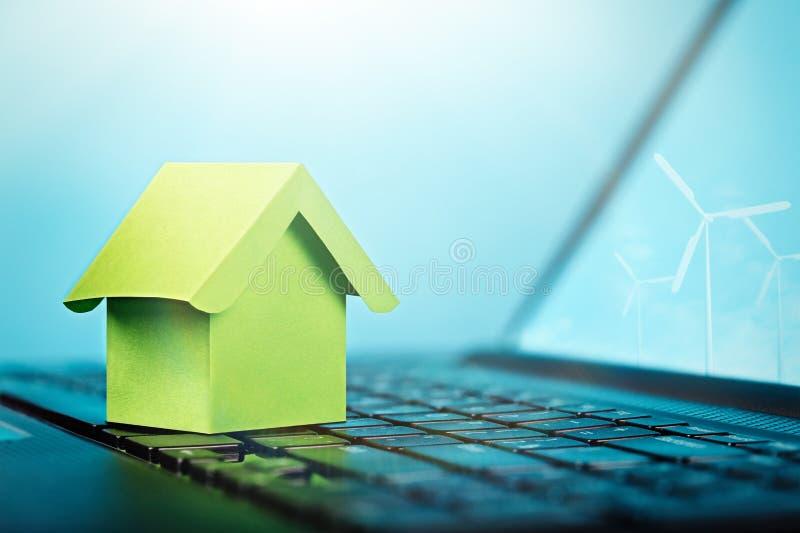 Grönt hus på tangentbordet och vindkraftväxter på datorskärmen Smart hus, ekologimakt, fastighet, förnybara energikällorconcep royaltyfria bilder
